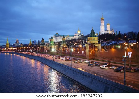 Traffic on Kremlin embankment against Ivan Great bell tower and Grand Kremlin Palace at evening in Moscow, Russia  - stock photo