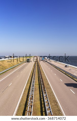 Traffic on the Afsluitdijk on a sunny day in The Netherlands. The Afsluitdijk is a dike over 32km damming off the former Zuiderzee, a salt water inlet of the North Sea. - stock photo