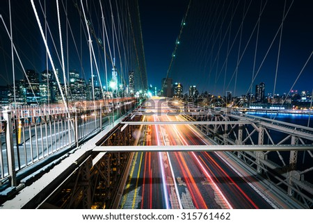 Traffic on the Brooklyn Bridge at night, in Brooklyn, New York. - stock photo