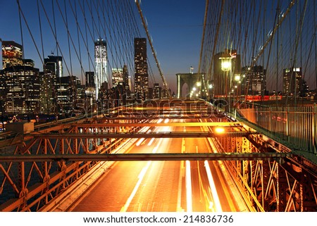 Traffic on the Brooklyn Bridge at night in New York - stock photo