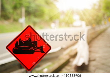 Traffic sign,construction tractor sign on blur damage road abstract background. - stock photo