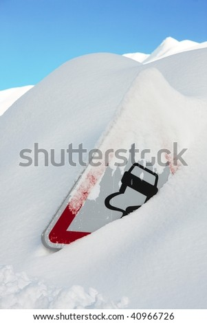 Traffic sign covered by a lot of snow - stock photo
