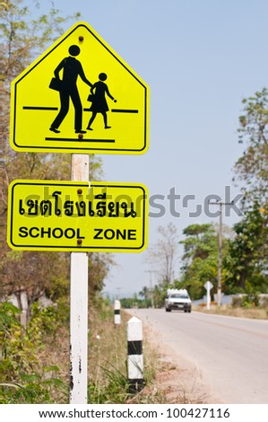 Traffic sign (School warning sign) with the Thai and English text.