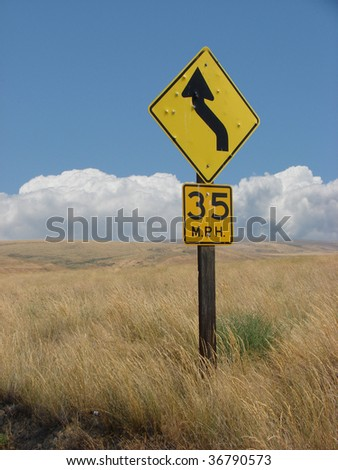 Traffic sign with bullet holes in wheat field - stock photo