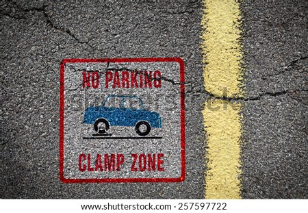 "Traffic signage of an illegally parked car on wheel clamp with the message ""no parking clamp zone"", painted on the surface of an asphalt road. - stock photo"