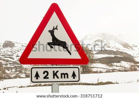 Traffic signal at danger , with the image of a deer, wild animals announces a distance of 2 km of road in snowy winter landscape  - stock photo
