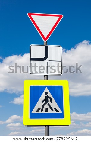 Traffic signs main road and pedestrian crossing with clouds in background - stock photo