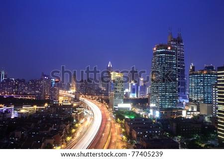 traffic through downtown at night - stock photo