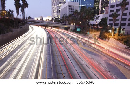 Traffic through Los Angeles at sunset - stock photo