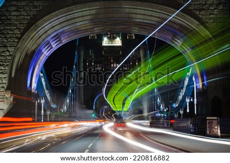 Traffic through Tower bridge at night - stock photo