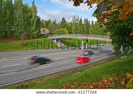 Traffic with motion blur (long exposure shot) on freeway. With bridge and autumn scenery on foreground - stock photo