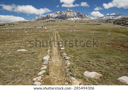 trail across the Humphreys Basin in the Sierra Nevada Mountains with Mount Humphreys on the horizon - stock photo