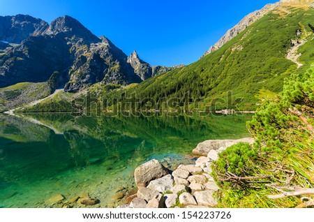 Trail at beautiful Morskie Oko green water alpine lake on sunny day, Tatry Mountains (High Tatras), Poland  - stock photo