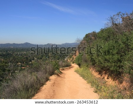Trail leading along a hill side beneath blue sky, California - stock photo