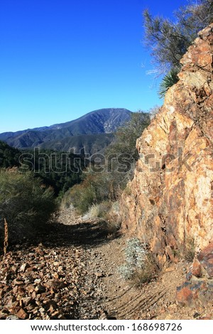 Trail leading along a hill side with geology and mountains, California - stock photo