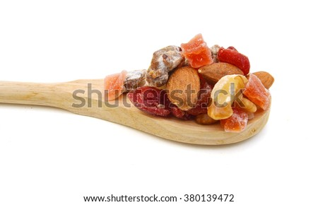 Trail mix isolated in wooden spoon on white.