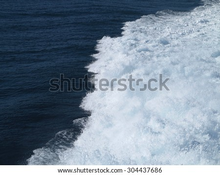 Trail on blue water surface behind of fast moving ferryboat - stock photo