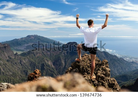 Trail runner, man and success in mountains, arms raised. Running, sports, fitness and healthy lifestyle outdoors in summer nature - stock photo