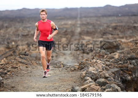 Trail runner - running man trail runner cross country training outdoors for marathon or triathlon. Male athlete working out on Hawaii, Big Island, USA. Triathlete listening to music on smart phone - stock photo