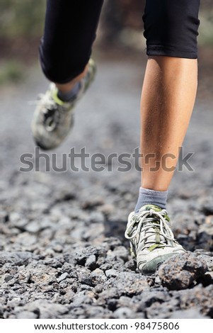 Trail runner woman running on mountain path with rocks. Running shoes and legs closeup of female fitness sport model during outdoor workout. - stock photo