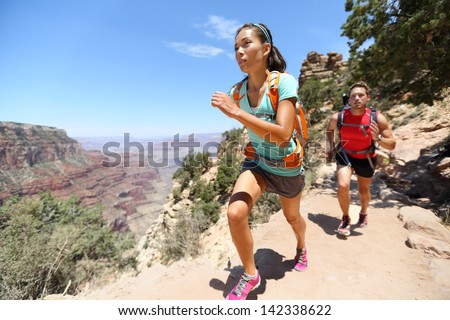Trail running cross-country runners in race on path in Grand Canyon, USA. Fit athletes jogging and training together in beautiful nature landscape. Asian fitness woman, Caucasian fit model. - stock photo