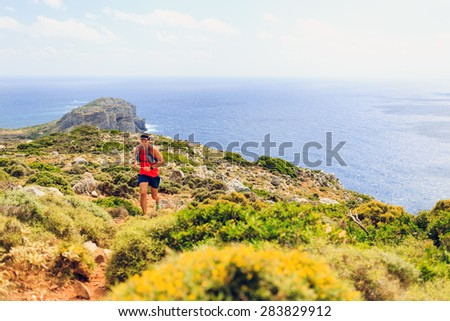 Trail running man cross country running in mountains on summer beautiful day Training and working out fitness healthy colorful runner jogging and exercising outdoors on rocky footpath on Crete, Greece - stock photo