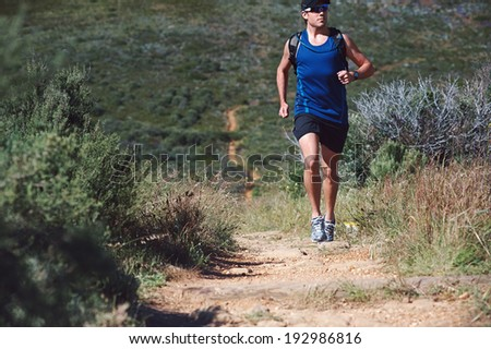 Trail running man exercising outdoors for fitness - stock photo