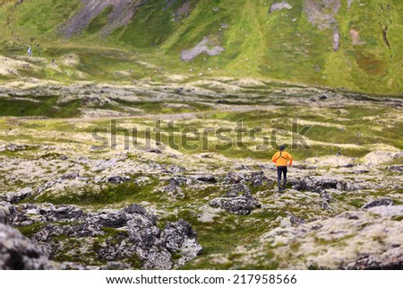 Trail running man in nature landscape doing cross country run. Fit male runner training jogging outdoors in beautiful mountain nature landscape with Snaefellsjokull, Snaefellsnes, Iceland. - stock photo