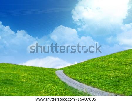 Trail running through grassy hills - stock photo