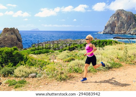 Trail running woman cross country running in mountains on summer beautiful day. Training and working out runner jogging and exercising outdoors in nature, rocky footpath on Crete, Greece - stock photo