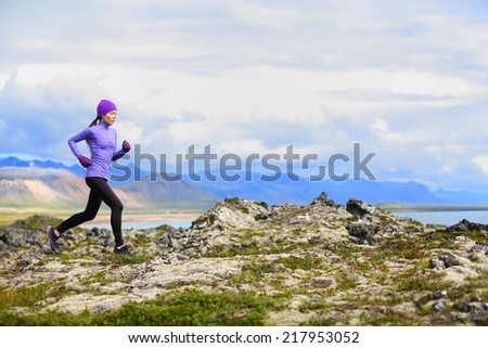 Trail running woman in cross country run. Female runner training jogging outdoors in beautiful mountain nature landscape on Snaefellsnes, Iceland. Healthy lifestyle with mixed race fitness model. - stock photo
