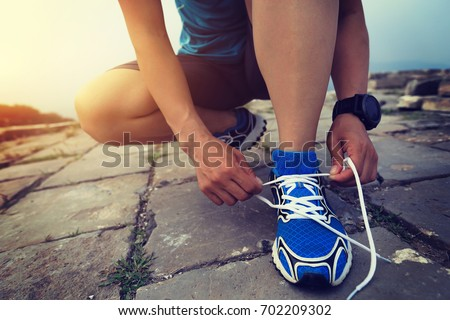 trail running woman runner tying shoelace before at great wall on the top of mountain
