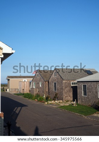 trailer mobile homes and cottages waterfront park Montauk New York Ditch Plains beach American flag blowing in the wind - stock photo