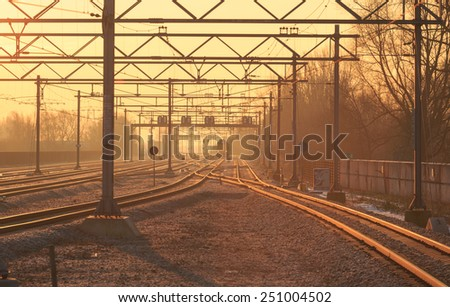 Train and railroad tracks during a yellow sunrise in winter. - stock photo