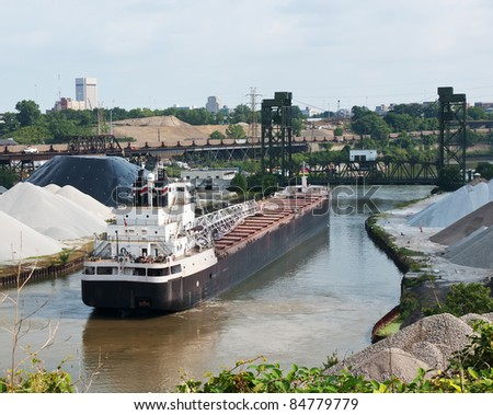 Train and Ship Two modes of industrial transportation including a Great Lakes bulk carrier ship waiting for a drawbridge to be raised and a line of railroad coal cars crossing an elevated viaduct - stock photo