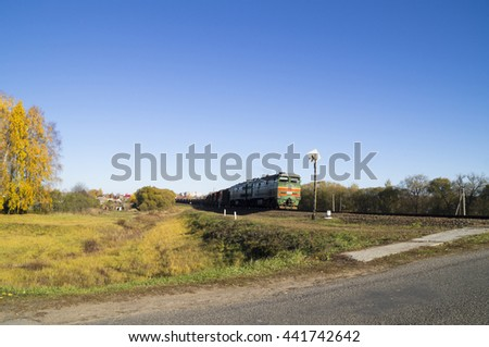 train approaching the railroad crossing - stock photo
