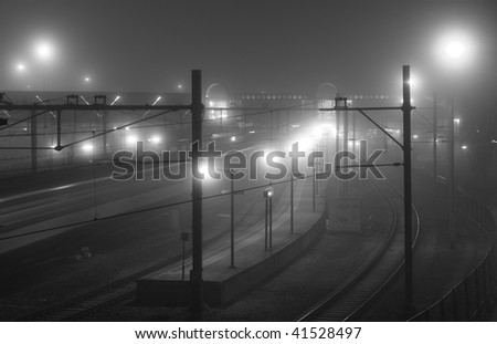 Train arriving at foggy railway station at night - stock photo