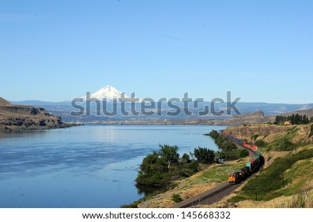 train at scenic Columbia River Gorge with visible Mt. Hood  - stock photo