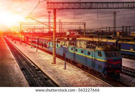 train awaits passengers on peron in the rays of the red sun