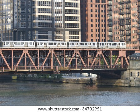 train on bridge over water with tall buildings in background