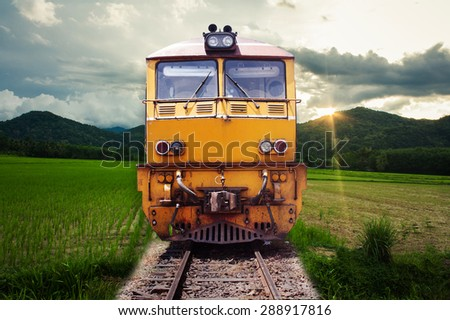 train passes through green field on the mountain background  - stock photo