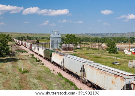 Train Passing Old Grain Elevator in South Dakota - stock photo