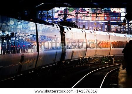 Train reflecting sunset sky - stock photo