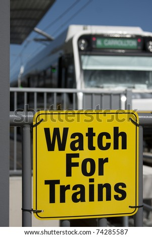 Train sign with train departing in the background