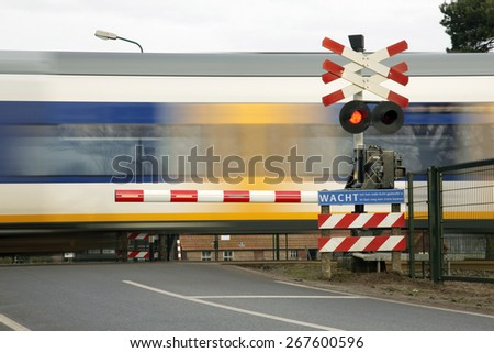 train speeding near railway crossing in the netherlands - stock photo