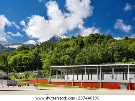 Train station with an area for car parking on the background hills - stock photo