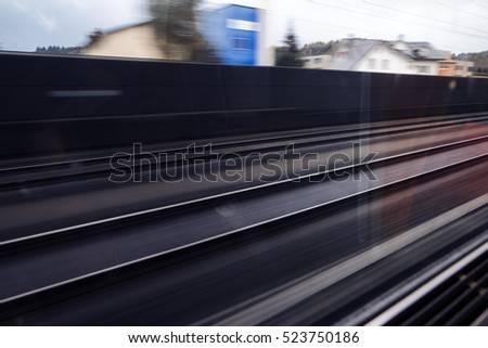 Train tracks as seen from inside a fast moving train, with motion blur