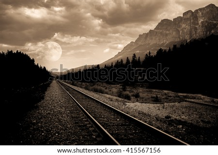 train tracks in a remote area with mountains and a full moon in a background in black and white, full moon, train track, full moon in nature, railroad or train track to the big full moon - stock photo