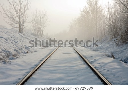 Train tracks in winter mist - stock photo