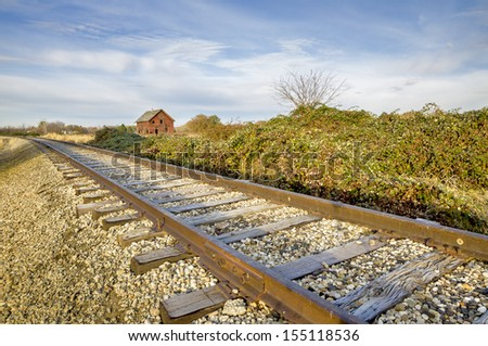 Train tracks lead past an old house - stock photo